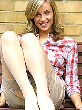 Melanie wearing a checked shirt and a cream mini skirt with white stockings and cotton panties.